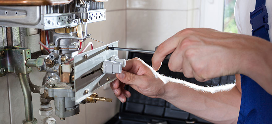 Handyman adjusting gas water heater