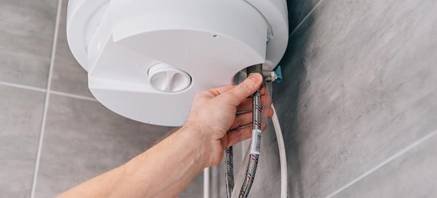 Cropped shot of male plumber repairing electric boiler